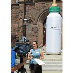 Elizabeth Saunders being interviewed in front of the giant baby bottle